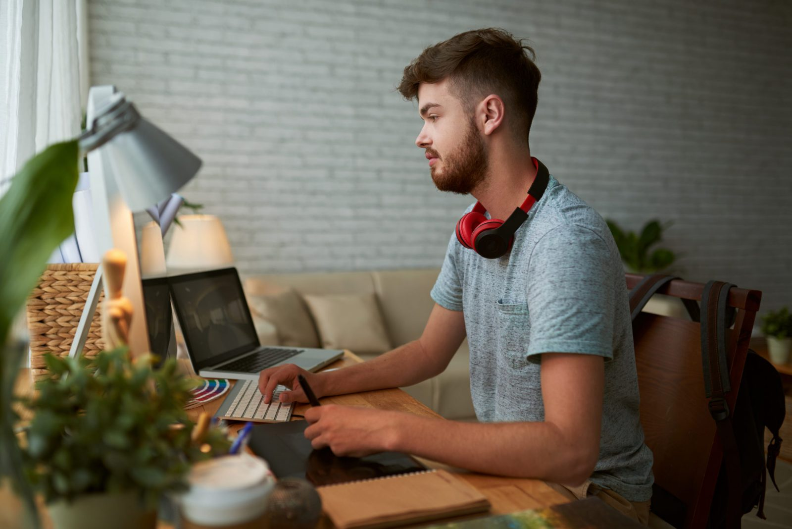 Side view of student working on computer at home